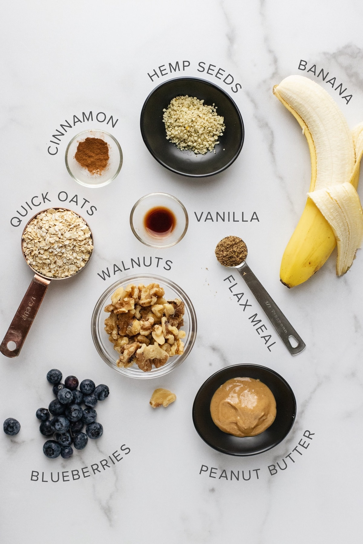 ingredients for an oatmeal bowl arranged on a white counter top.