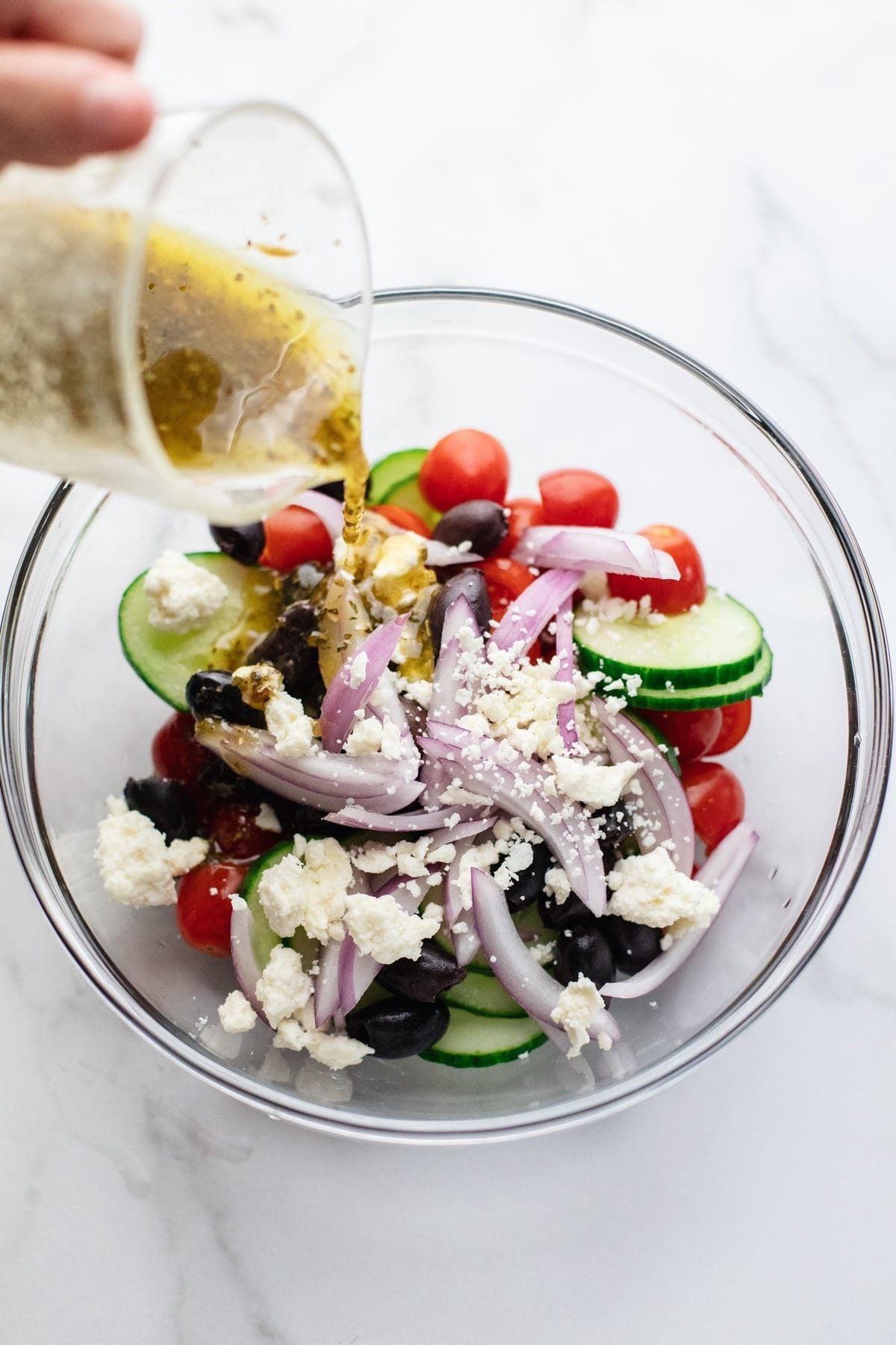 Dressing being poured over a greek salad.