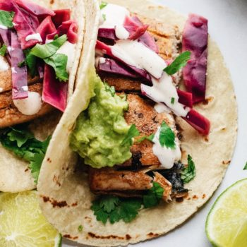 Fish tacos on a white counter with purple cabbage and guacamole on top.