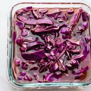 Square glass bowl with pickled cabbage in it.
