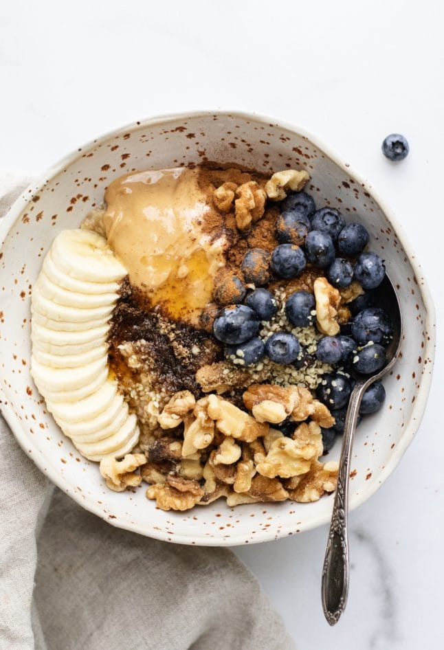 A ceramic bowl with oatmeal, banana slices, nuts, and blueberries with a spoon in it.