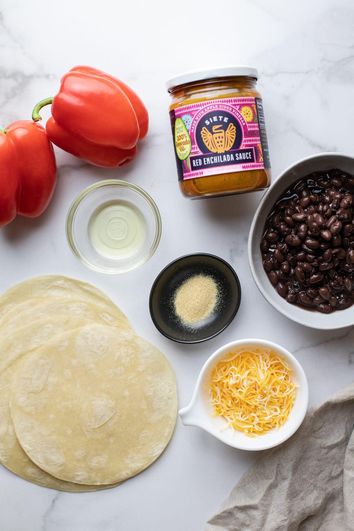 Enchilada ingredients arranged on top white counter top.