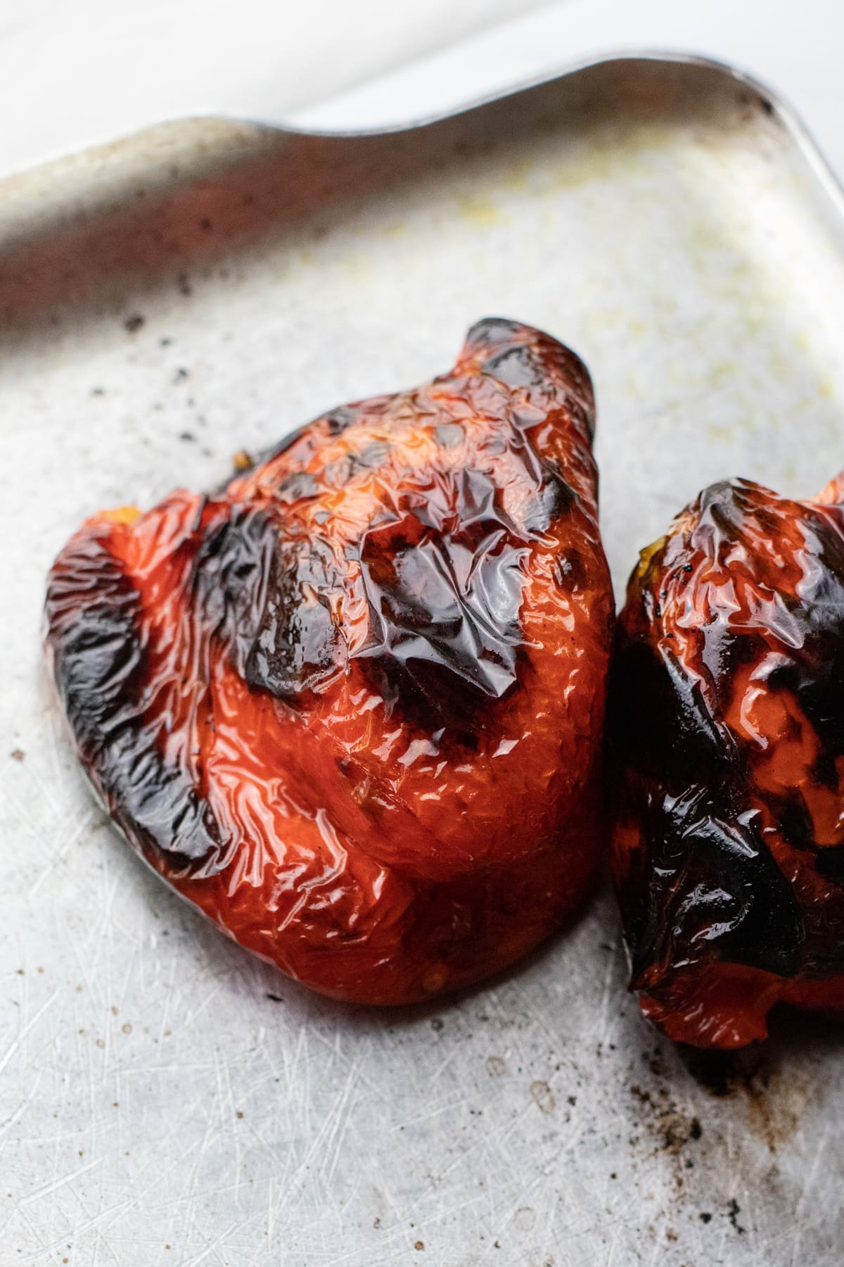Charred red pepper on stainless steel pan.