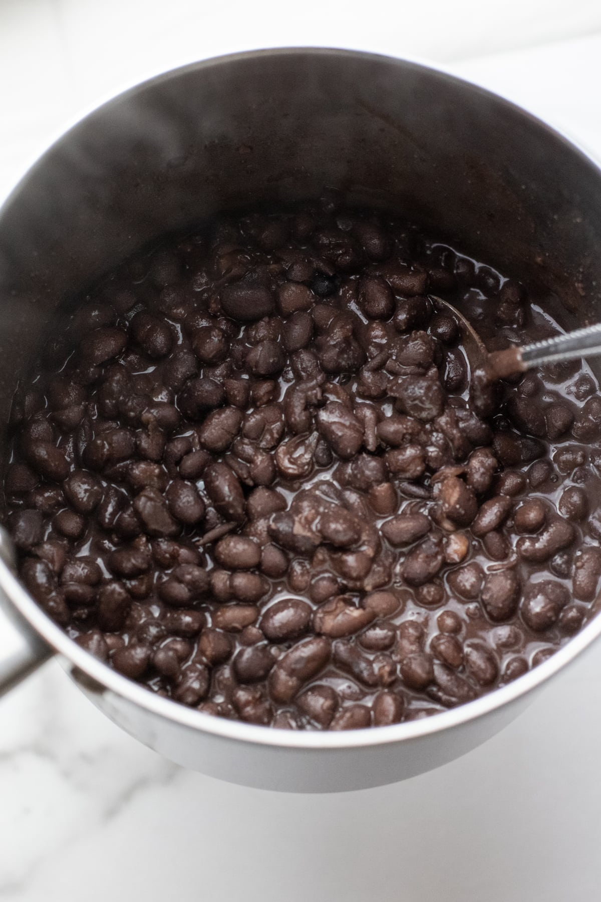 black beans cooking in a stainless steel pot.