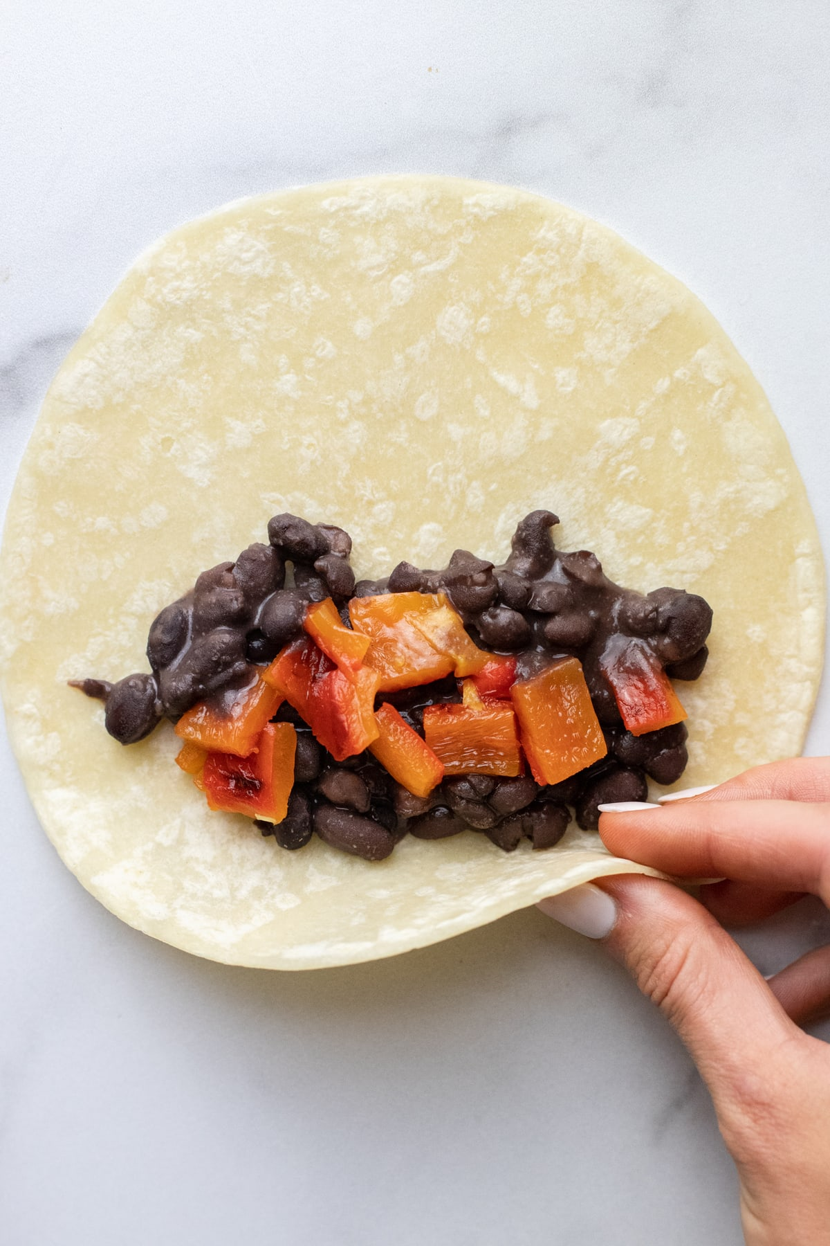 A hand wrapping a tortilla with black beans in it.