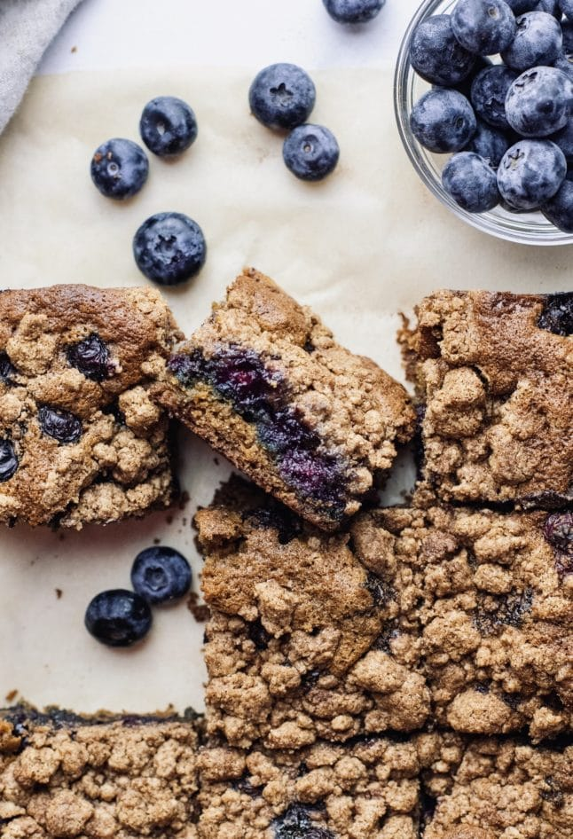 Blueberry crumb cake slices arranged on parchment paper with blueberries sprinkled around them.