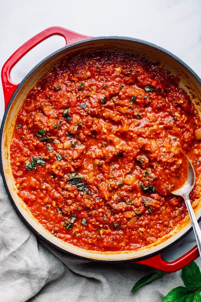 red pan with fresh tomato sauce in it with a silver spoon.