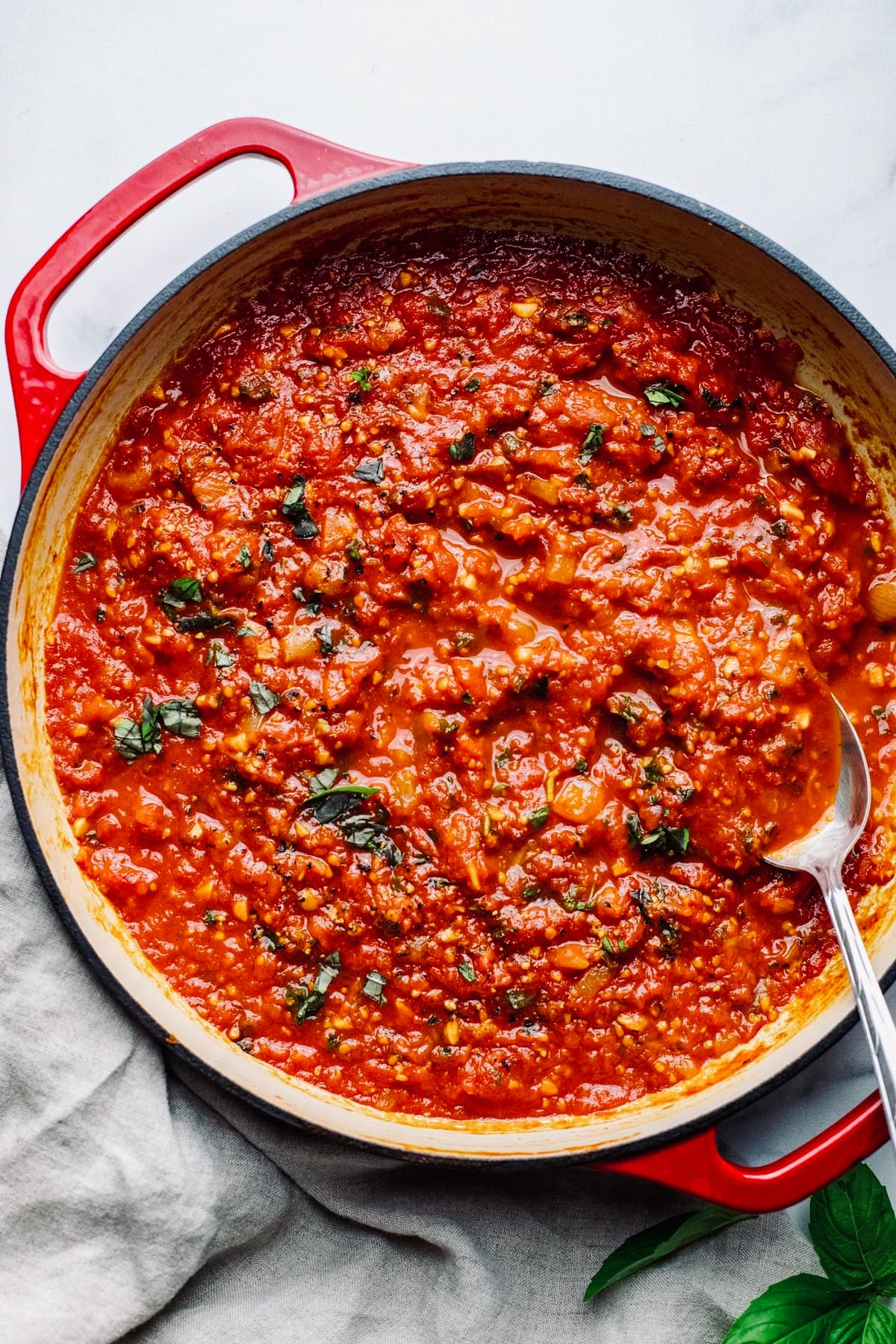 red pan on white background with fresh tomato sauce in it.