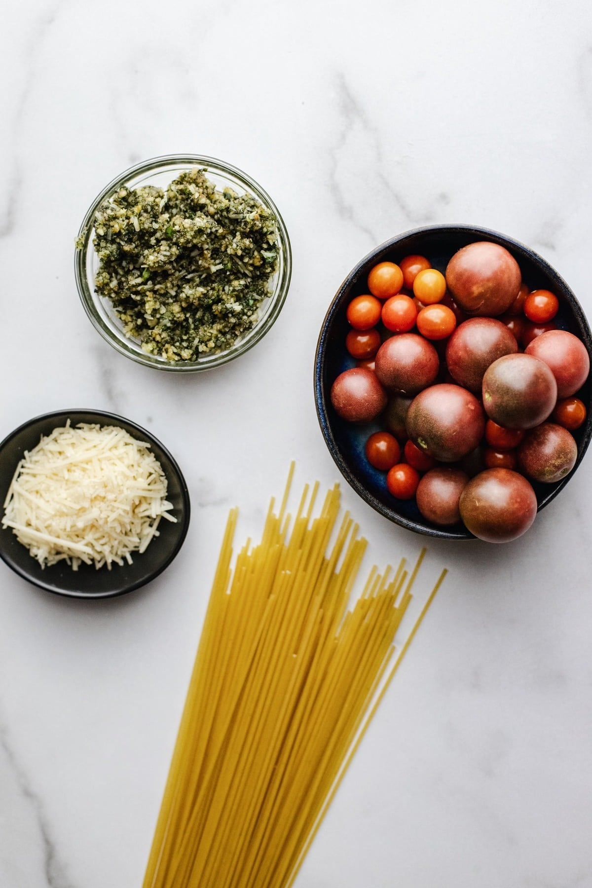 Ingredients for spaghetti pesto arranged on a white counter.