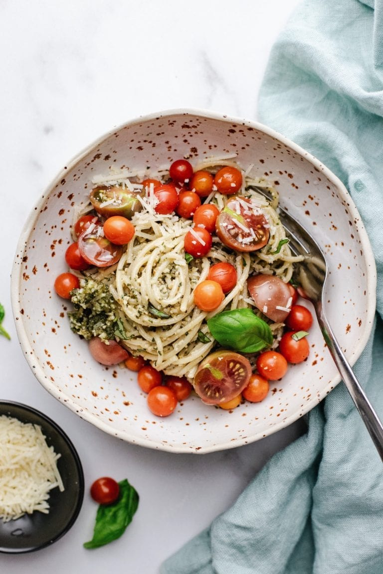 A ceramic bowl with spaghetti and cherry tomatoes in it on a white counter with a blue napkin next to it.