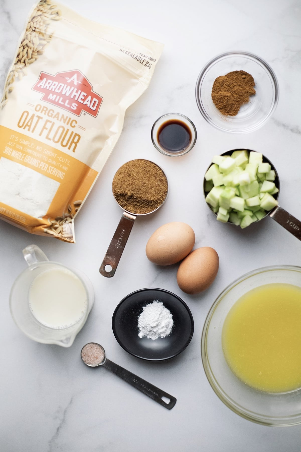 Ingredients for apple streusel bread arranged on top white counter.