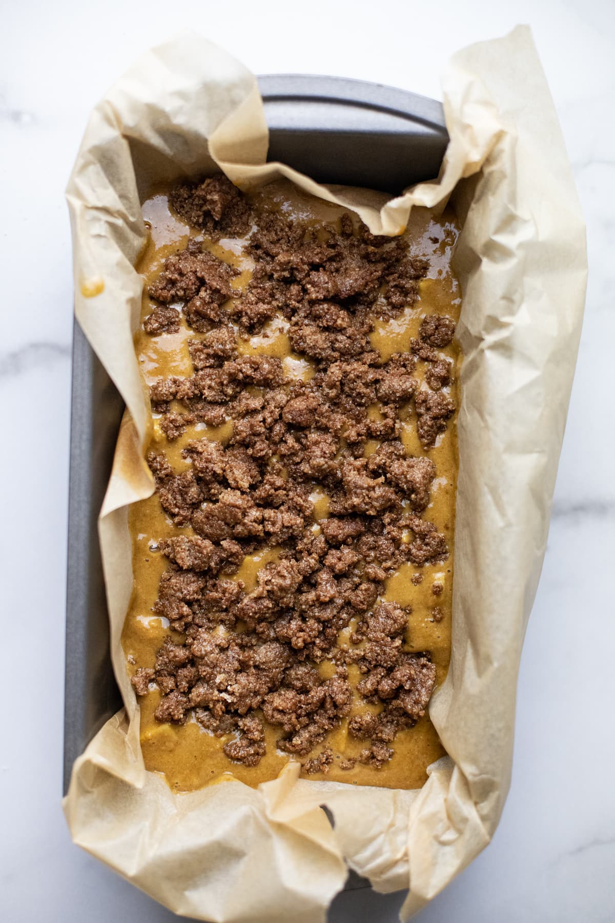 Apple cake batter in a pan lined with parchment paper.