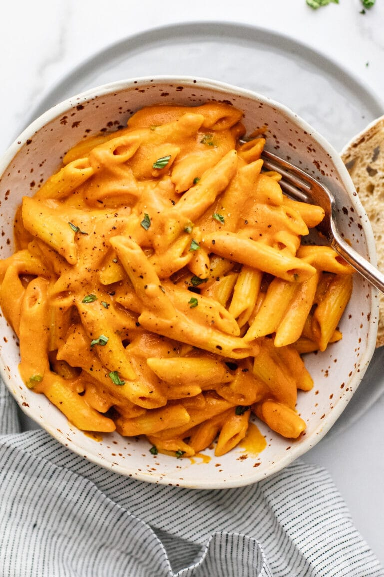 Ceramic bowl with chickpea pasta in red pepper sauce.