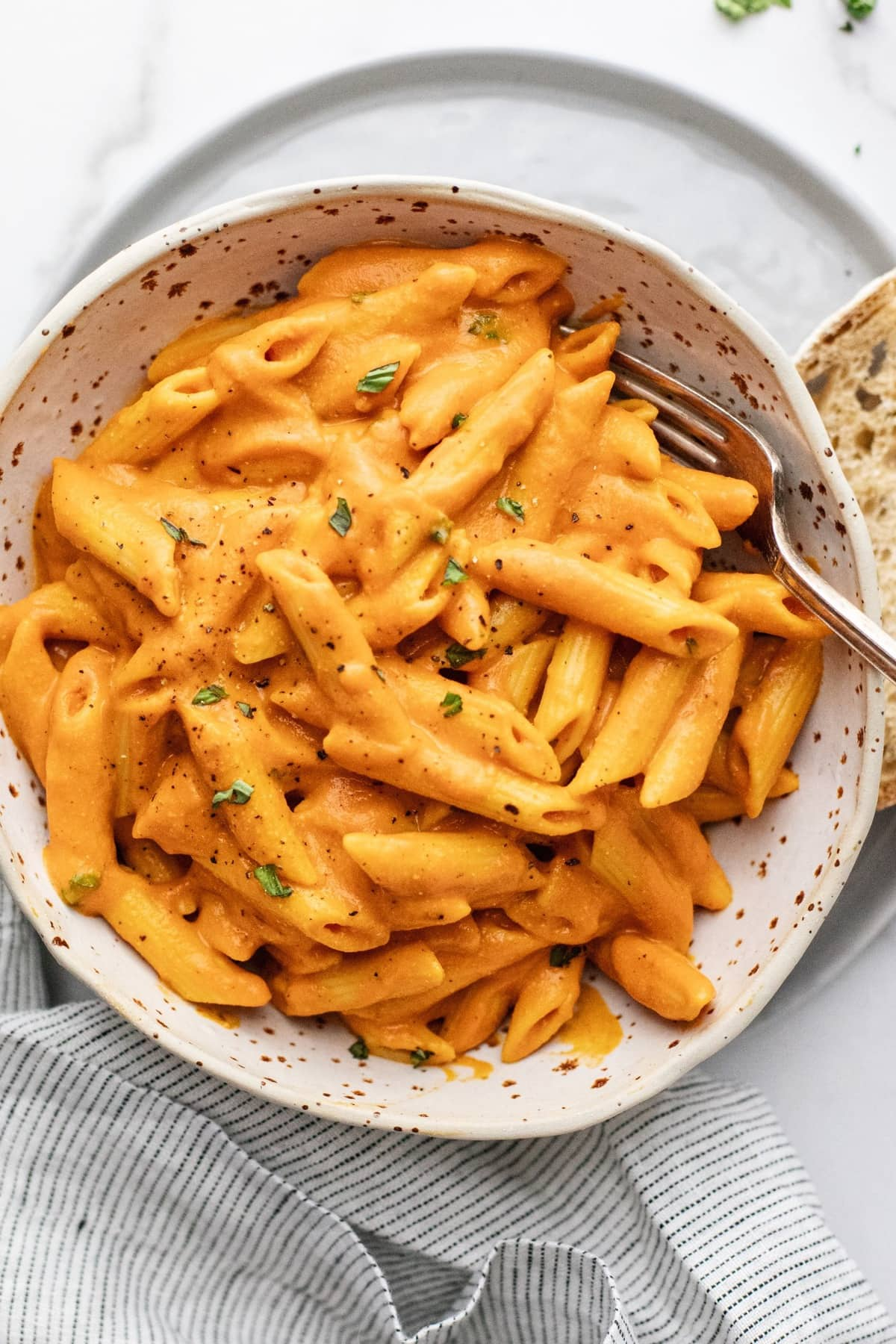 Ceramic speckled bowl on gray plate with penne pasta in a bright orange pepper sauce in it.