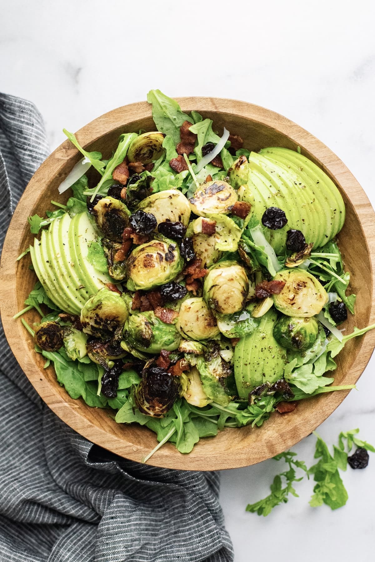A wooden bowl filled with salad, green apples, and cooked brussels sprouts on top.