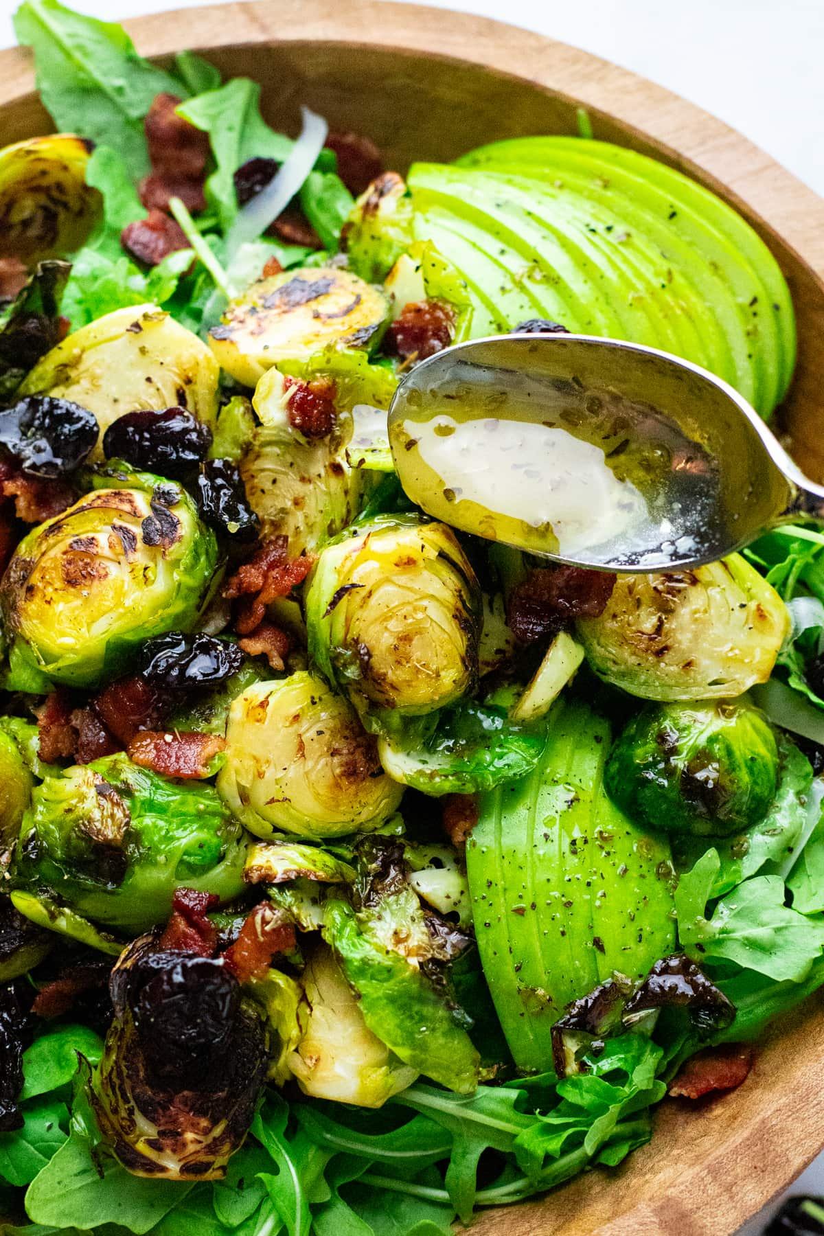 Spoon pouring salad dressing over salad with brussels sprouts and bacon.