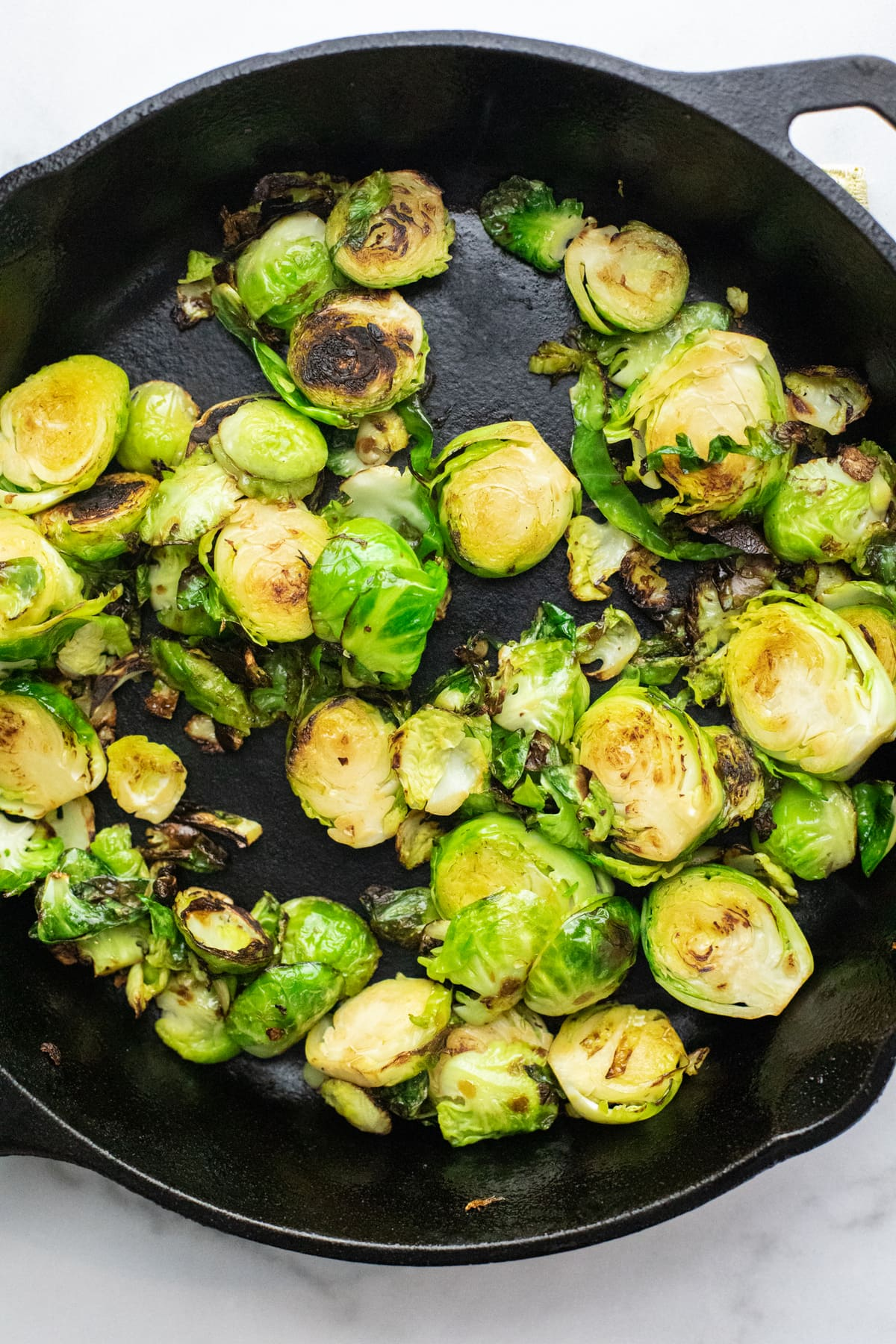 Sliced brussels sprouts being sautéed in black cast iron skillet.