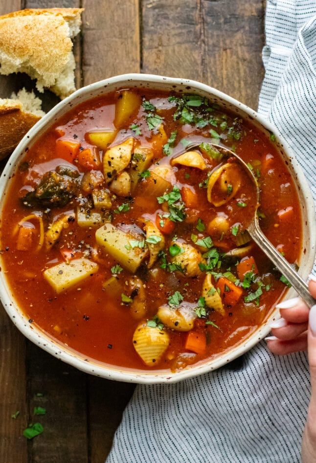 Hand holding spoon in bowl of vegetable soup on wooden board with torn bread in top corner and napkin next to bowl.