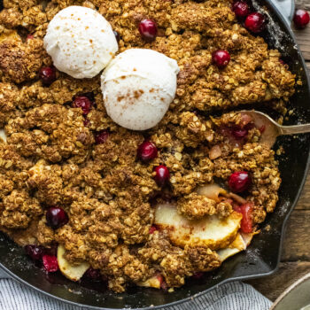 A gray cast iron skillet with apple cranberry crisp in it with two scoops of vanilla ice cream on top.