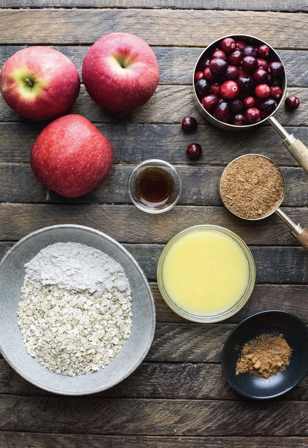 Ingredients for apple cranberry crisp arranged on a brown wooden board.