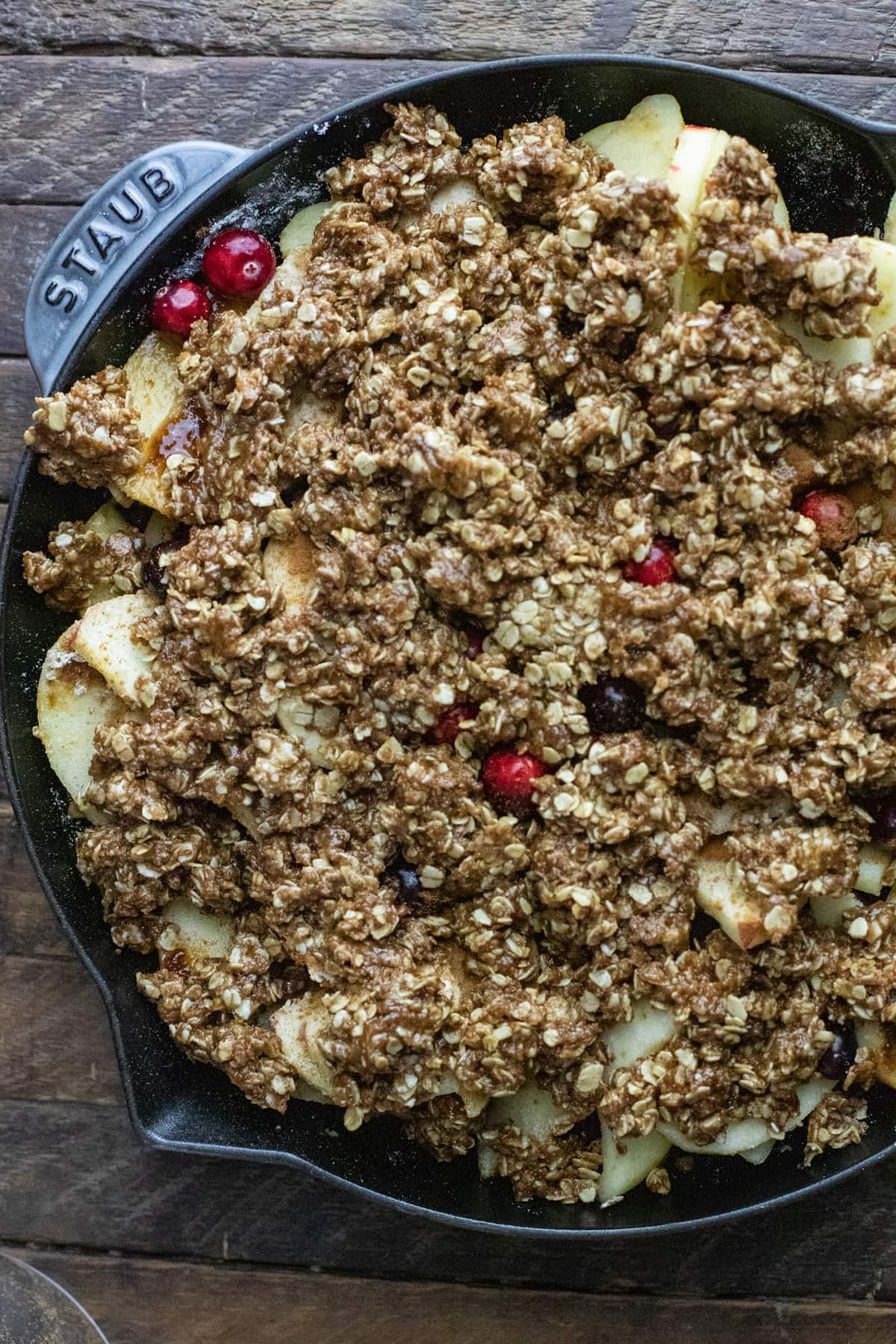 Cast iron skillet with cranberry and apples topped with an oat crumble.
