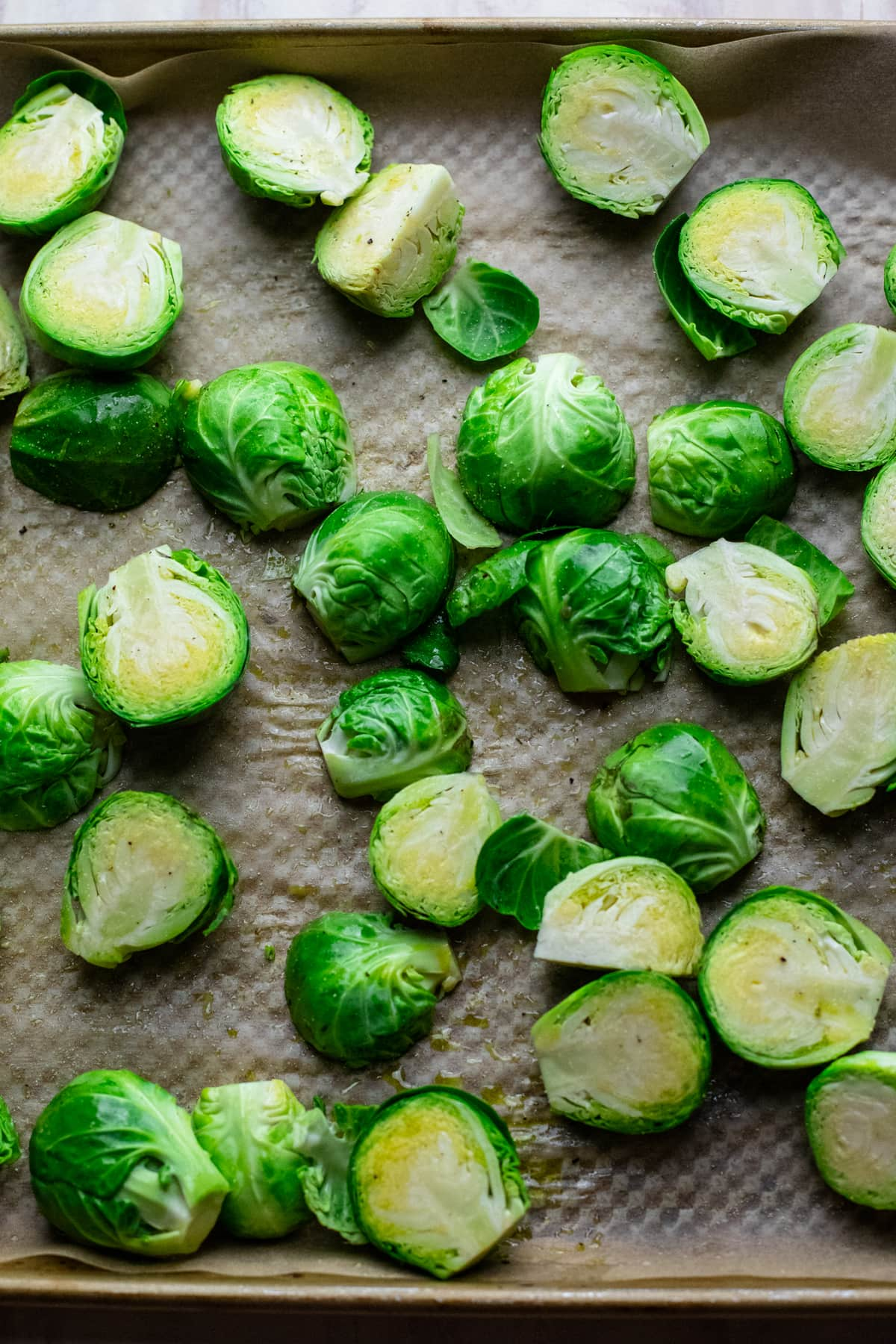 Sliced brussels sprouts on baking tray lined with parchment paper.