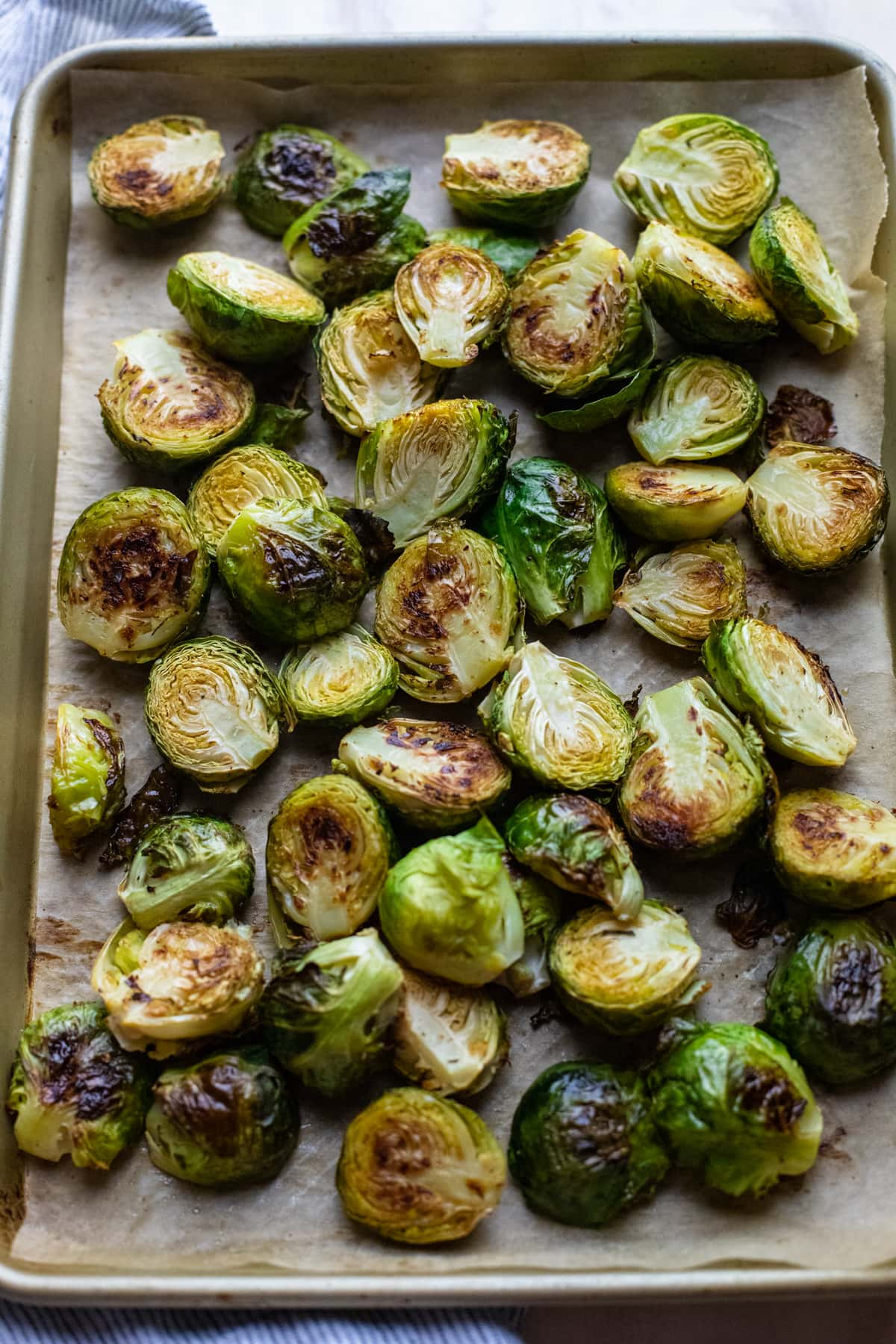 roasted brussels sprouts on gold baking sheet lined with parchment paper.