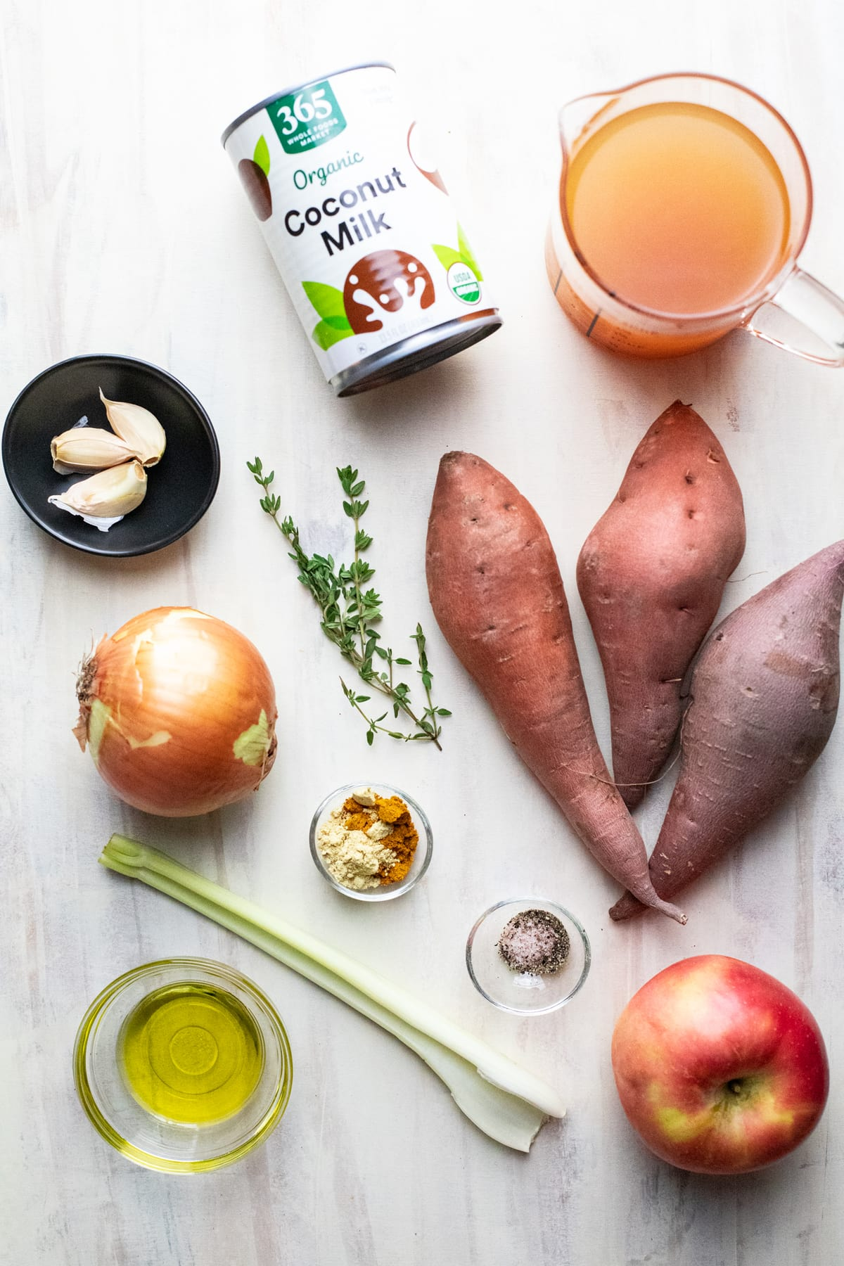 Ingredients for sweet potato bisque arranged on a white background.