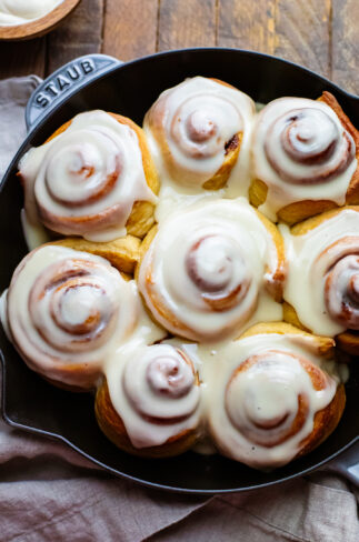 dairy free cinnamon rolls with icing on top in a cast iron skillet.