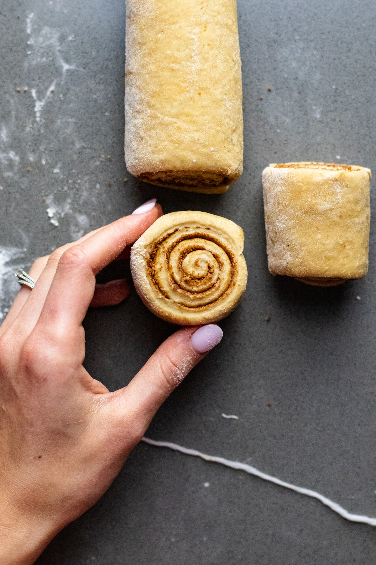 hand holding cinnamon roll spiral on gray counter.