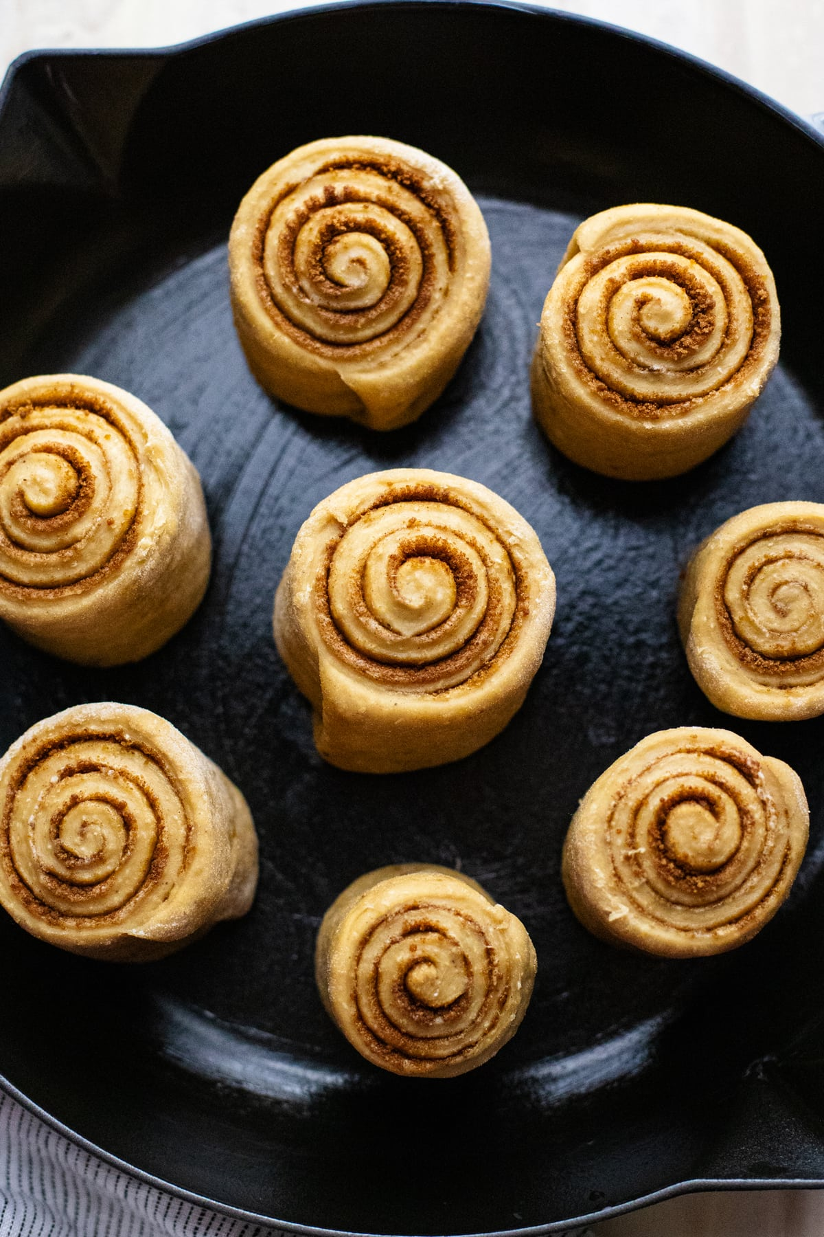 Raw cinnamon rolls in greased skillet.