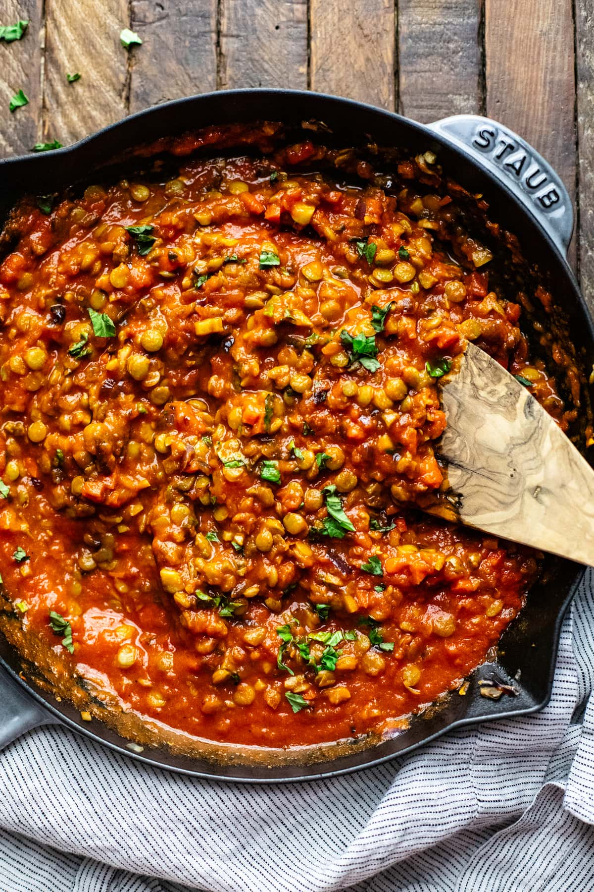 A cast iron skillet with red lentil bolognese sauce in it with wooden spoon.