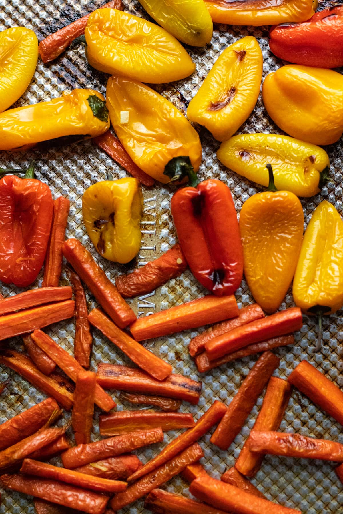 roasted chopped carrots and mini peppers on sheet pan.