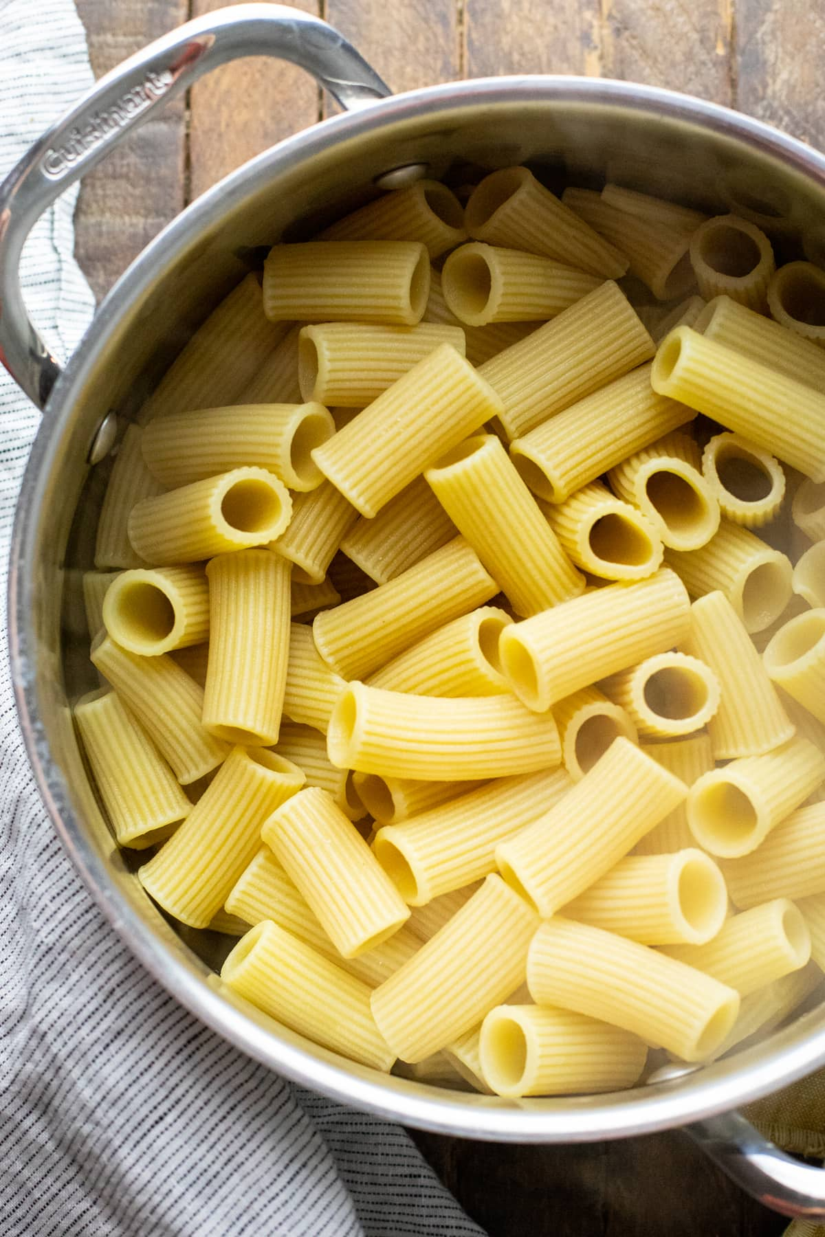 cooked rigatoni pasta noodles in cast iron pot.