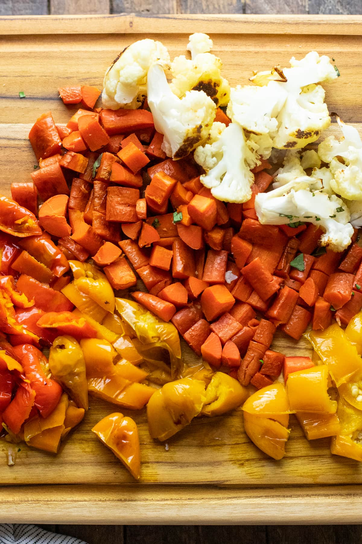 roasted vegetables chopped into pieces on wooden cutting board.
