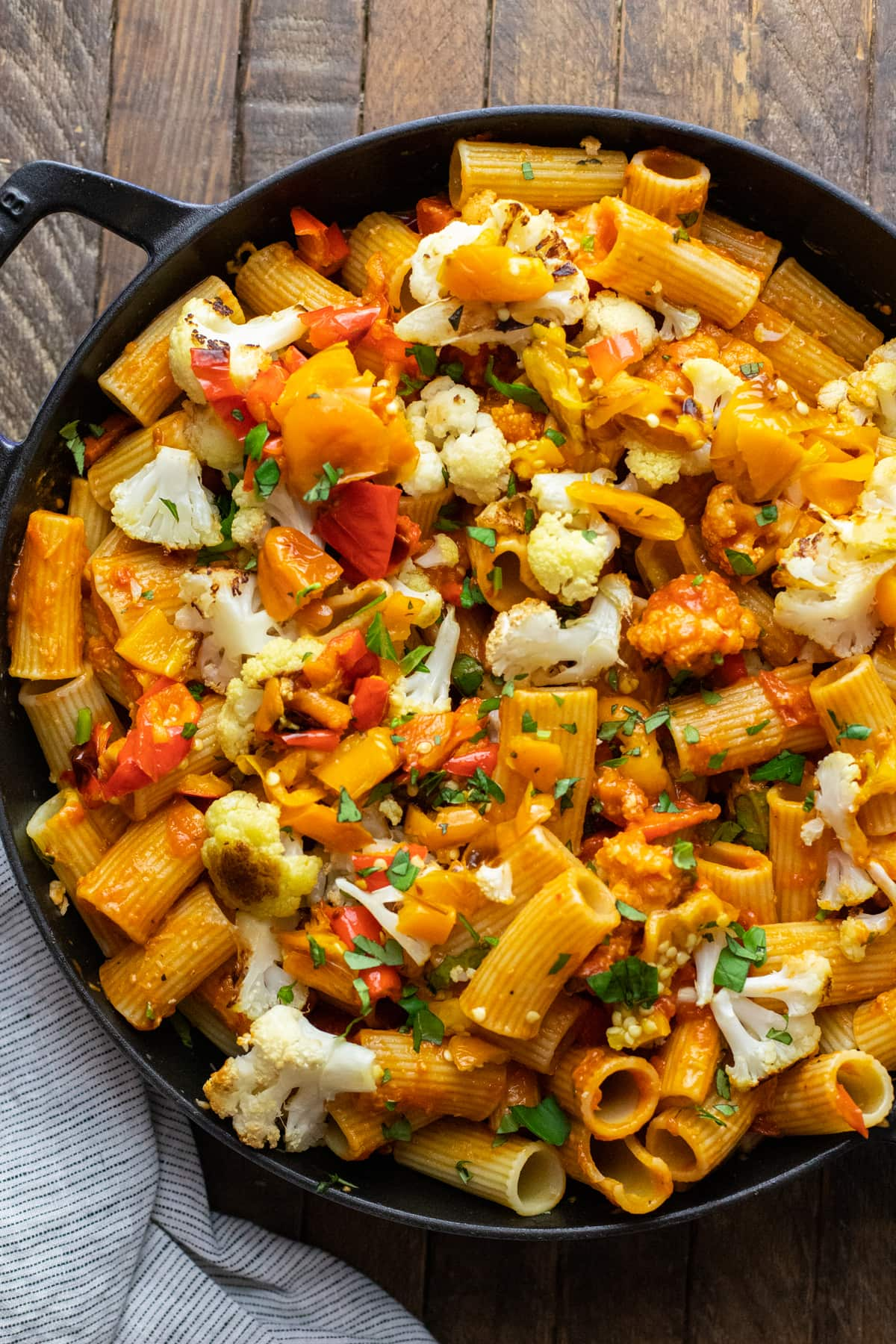 Cast iron pot with pasta noodles and roasted vegetables.