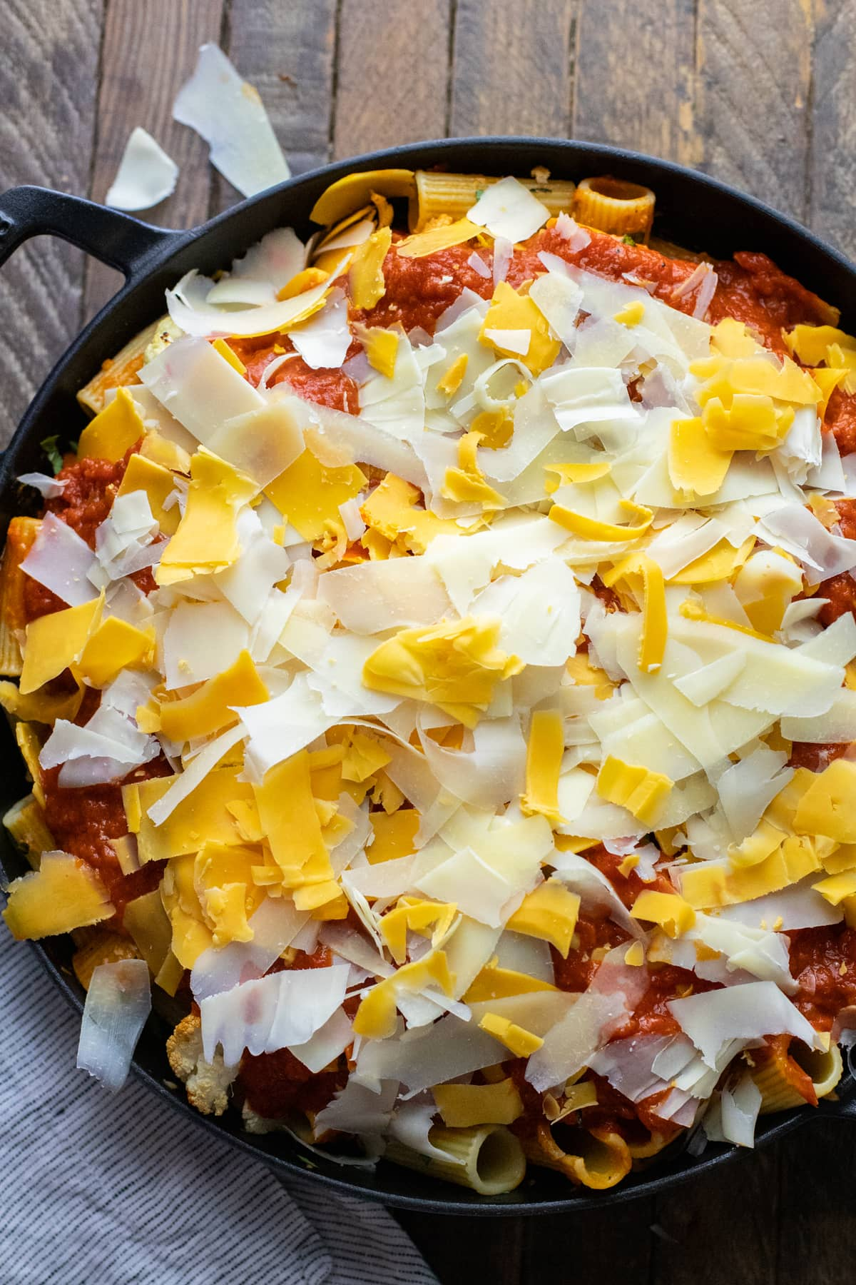 black cast iron pot with baked rigatoni and shredded cheese over top.