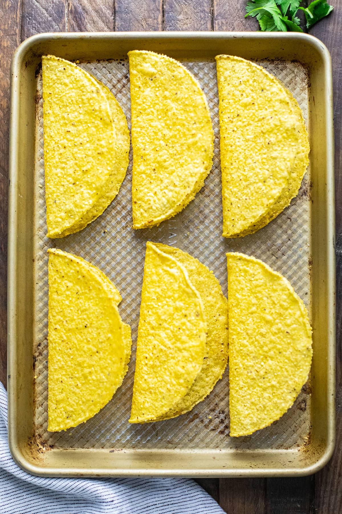 hardshell tortillas on a baking sheet pan.