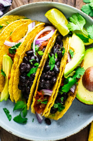 a group of black bean tacos on plate with condiments.