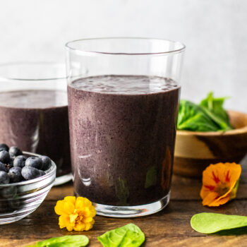 glasses filled with blueberry smoothie with blueberries and spinach leafs arranged around it.