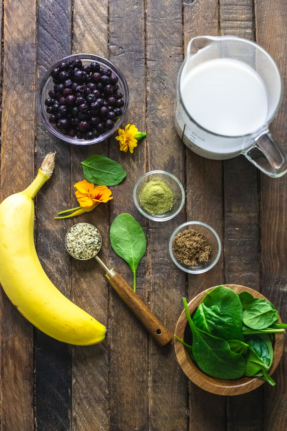 Ingredients for a blueberry spinach smoothie arranged on a wooden background.