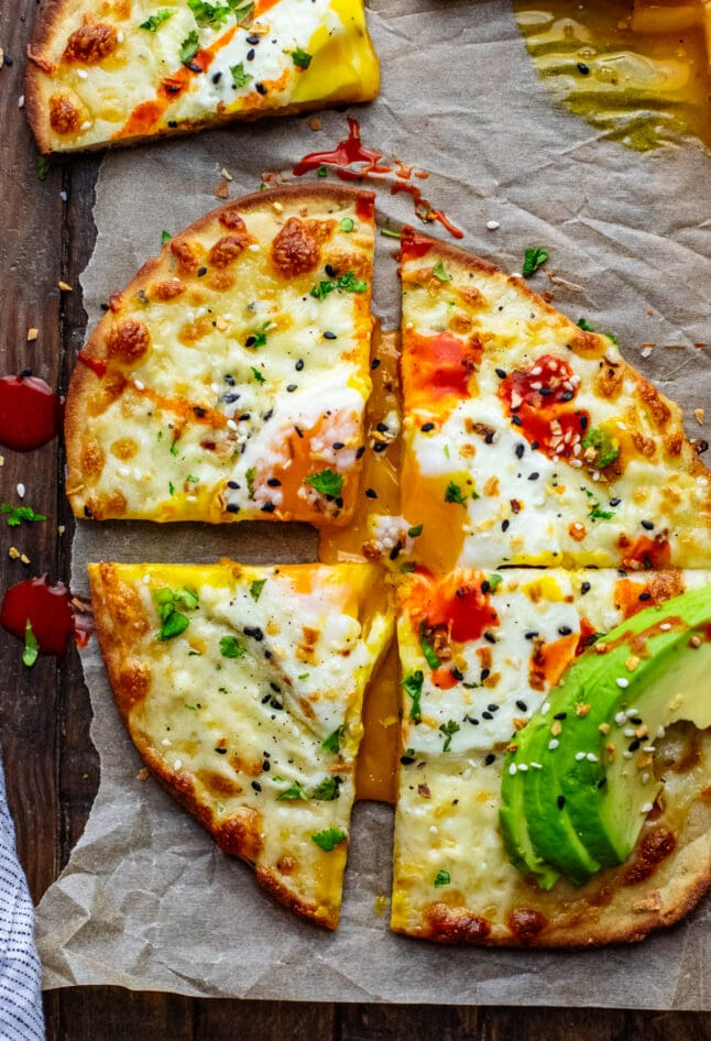 Naan breakfast pizza on parchment paper cut into 4 slices with running egg in center.