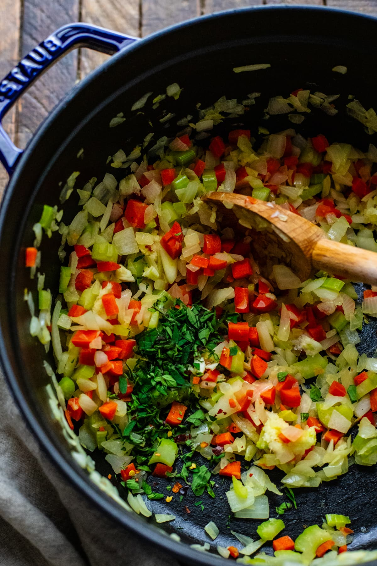 wooden spoon stirring chopped vegetables and herbs in cast iron pot.