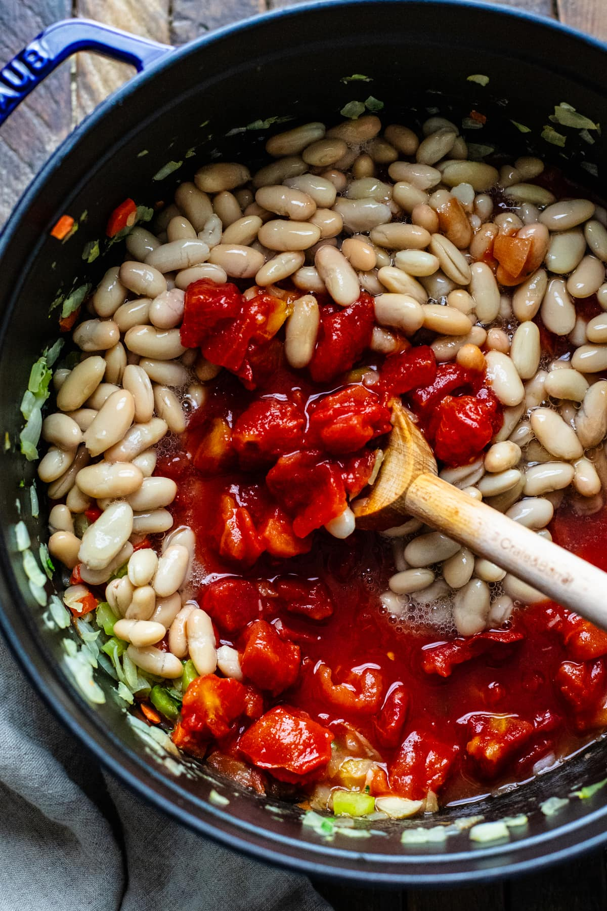 wooden spoon stirring diced tomatoes with white beans.