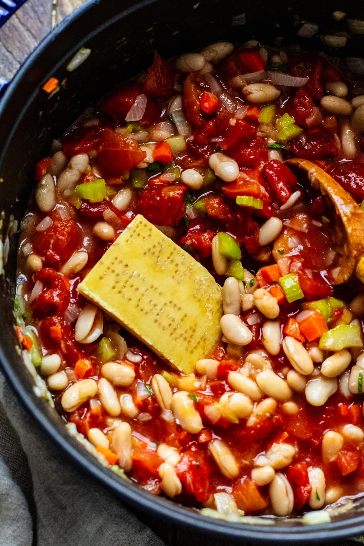 parmesan rind in a pot with tomatoes and white beans.