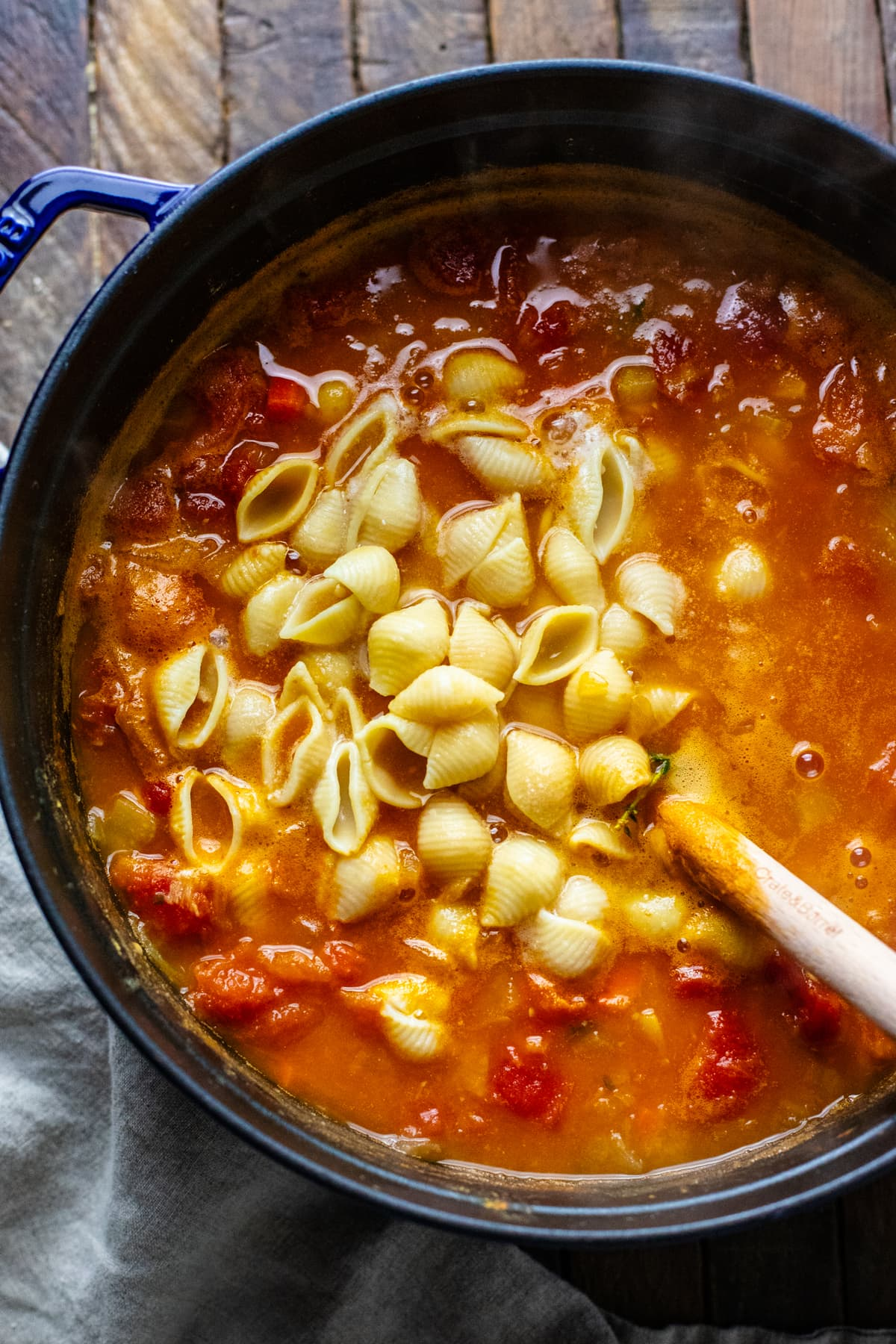 a black pot with red soup in it with pasta shells being mixed in.