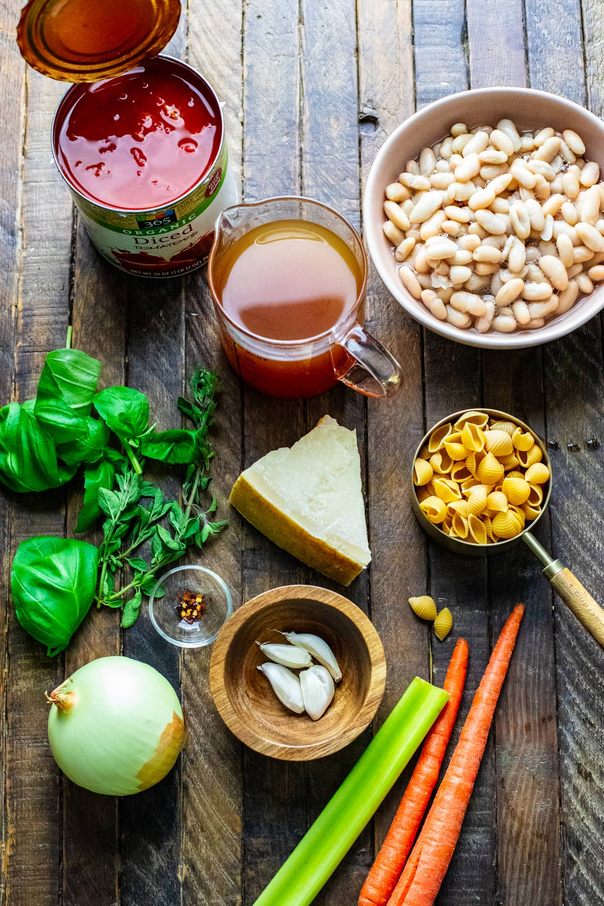 ingredients for pasta fagioli soup arranged on brown wooden board.