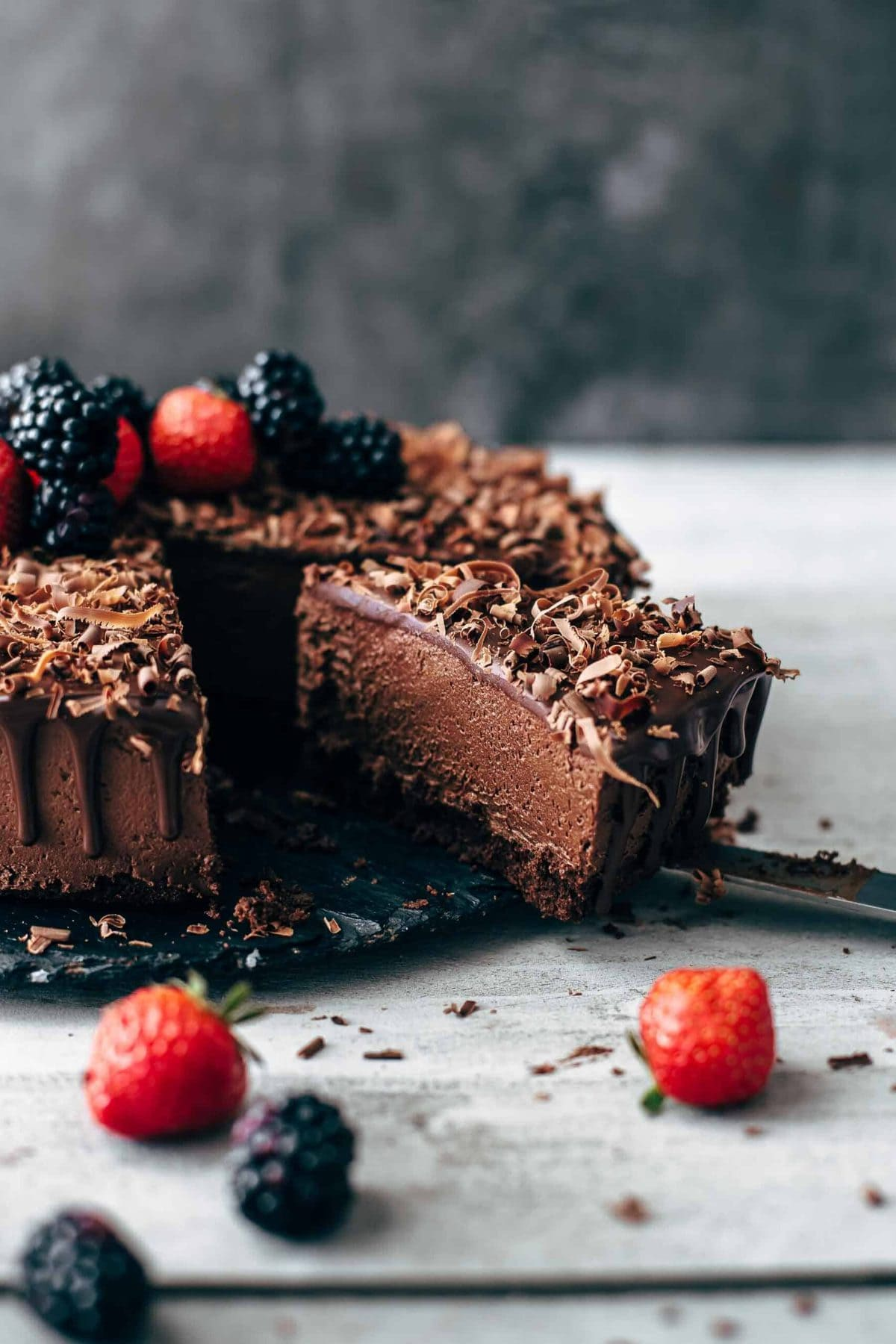 A slice of chocolate mousse cake with berries on top.
