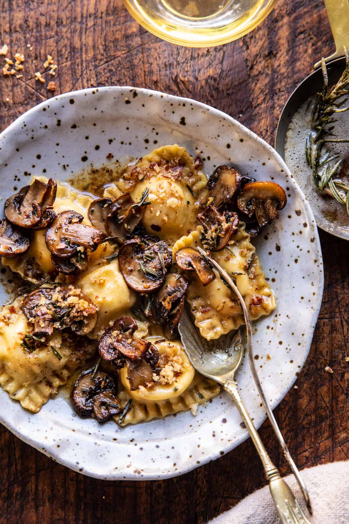mushrooms and raviolis on a speckled ceramic dish.