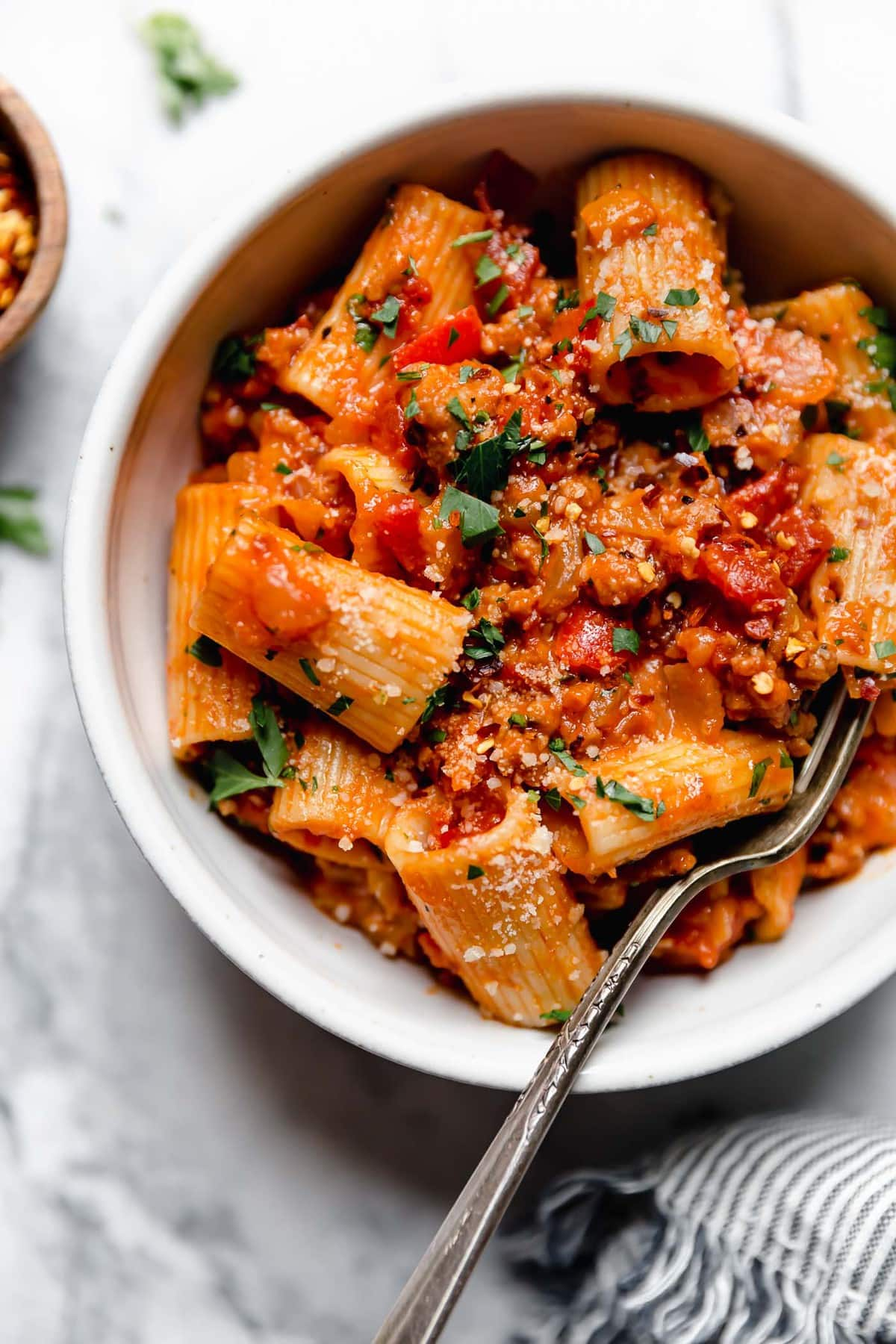 white bowl with rigatoni noodles in red Italian sausage and peppers sauce.